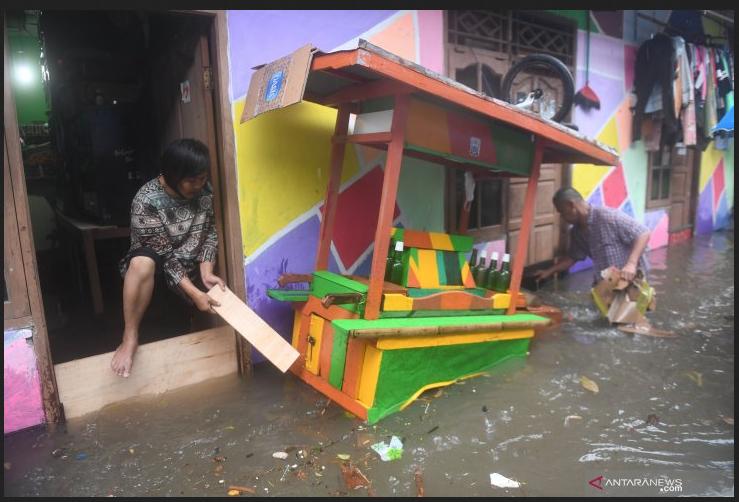Warga membersihkan sampah yang terbawa air saat banjir merendam kawasan RW 5, Duren Tiga, Pancoran, Jakarta, Kamis (18/2/2021). ANTARA FOTO/Akbar Nugroho Gumay/wsj.